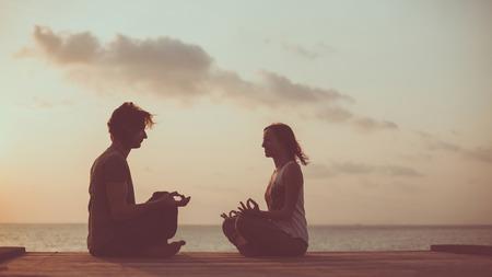 position d amour: Jeune couple est en train de faire du yoga sur l'arrière-plan du lever du soleil. tonification artistique.