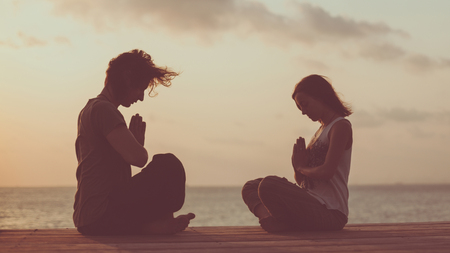 2 people: Young couple is doing yoga on the sunrise background. Artistic toning. Stock Photo