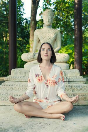 ancient yoga: Young woman is doing yoga on the ancient Buddha statue background.