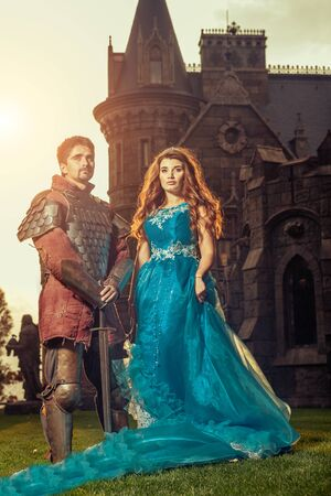 period costume: Medieval knight with his beloved lady. Ancient castle on the background.