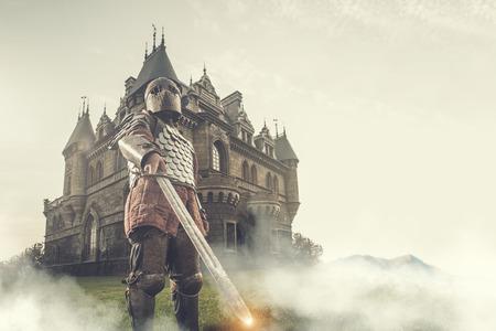 Caballero medieval con la espada en el fondo antiguo castillo. Bajo el procesamiento posterior contraste. Foto de archivo - 52920942