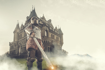 Medieval knight with the sword on the ancient castle background. Low contrast post processing. Stockfoto