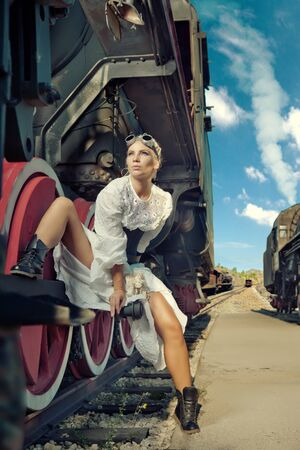 Woman in the vintage dress is sitting on the locomotive's wheel. Banco de Imagens