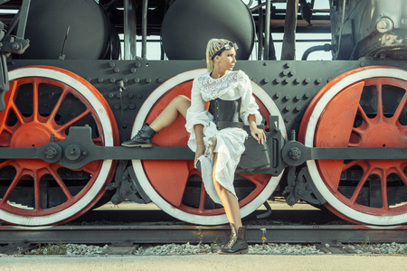 Woman in the vintage dress is sitting on the locomotive's wheel. Imagens - 52921030