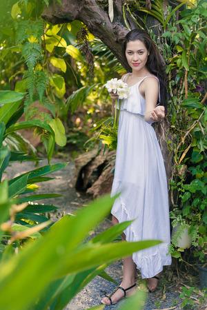 invitando: Mujer joven con el ramo de orquídeas que le invitan en las selvas.