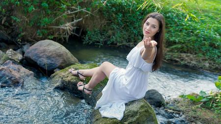invitando: Mujer joven en el vestido blanco que le invita en el agua.