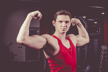 muscular build: Powerful man with muscular build is posing in the gym. Artistic toning.