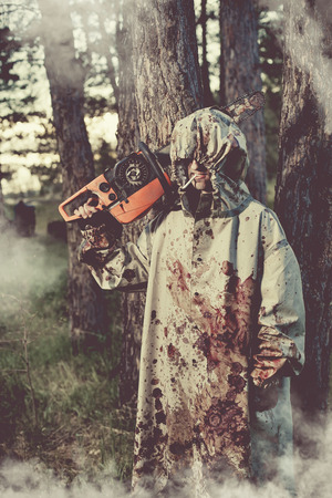 aggression: Smoking maniac with the chainsaw dressed in a dirty bloody raincoat. Artistic toning. Stock Photo
