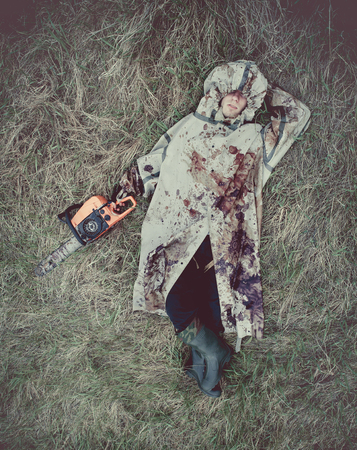 maniac: Relaxing maniac with the chainsaw dressed in a dirty bloody raincoat. Artistic toning.