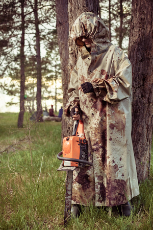 capote: Smoking maniac with the chainsaw dressed in a dirty bloody raincoat. Artistic toning. Stock Photo