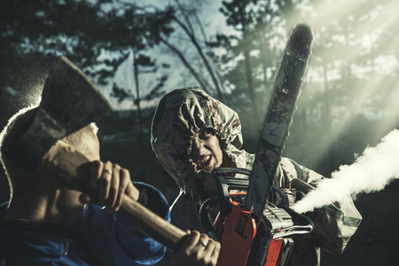 madman: Woman fights with the maniac, axe against chainsaw. Artistic toning. Stock Photo