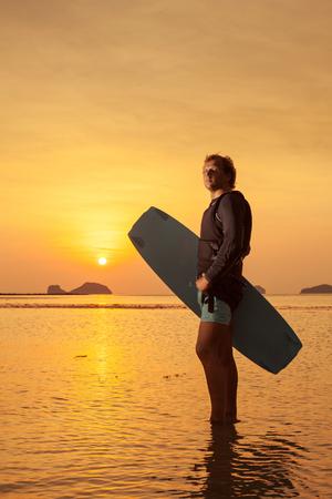homme blond avec le wakeboard sur le coucher de soleil tropical fond. Koh Samui, en Thaïlande.