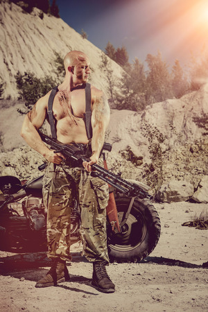 semi dress: Powerful soldier with the machine gun. Desert background. Stock Photo