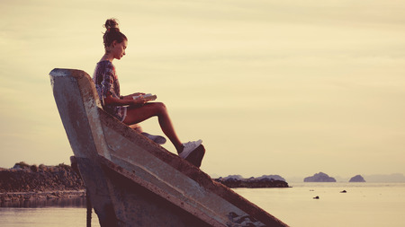 sunken boat: Young woman is sitting on shipwreck and reading a book. Tropical sunset on the background. Stock Photo