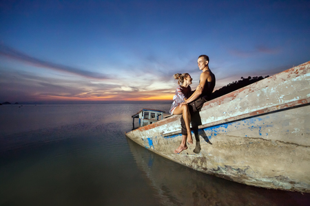 sunken boat: Young laughing couple is sitting on the sunken ship on the tropical sunset background.