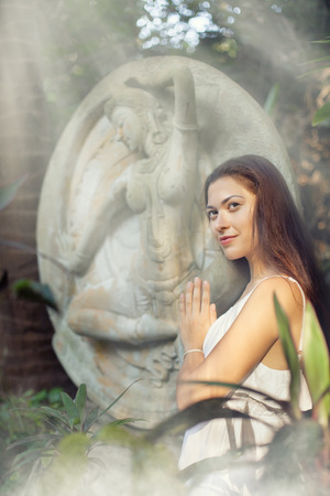ancient yoga: Young woman is doing yoga on the ancient statue background.