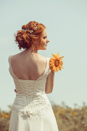 haired: Beautiful red haired bride on the sunflowers field background.