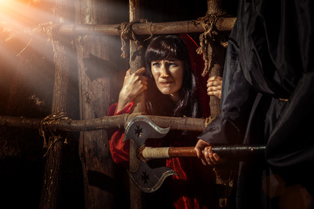 Beautiful witch in red dress in the dungeon is looking on the sunray. Stock Photo