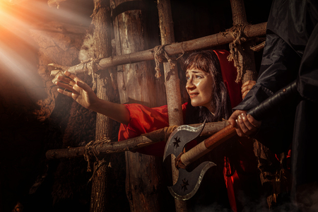 inquisition: Beautiful witch in red dress in the dungeon is looking on the sunray. Stock Photo