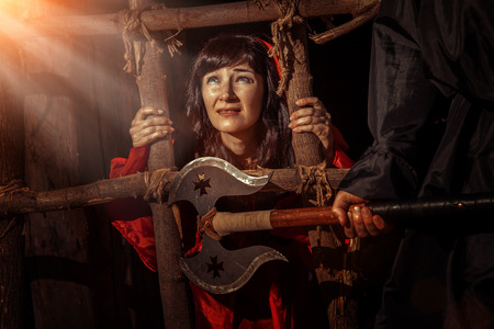 inquisition: Beautiful witch in red dress in the dungeon is looking on the sun ray. Stock Photo