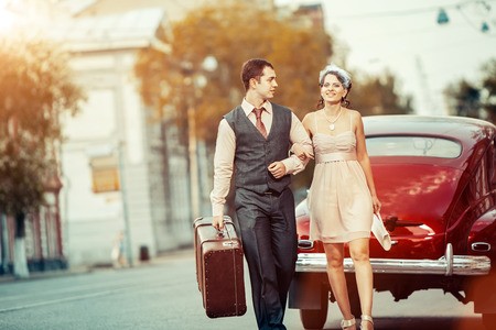 affectionate action: Pretty walking couple with the suitcase on the vintage car background.