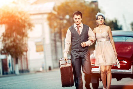 affectionate actions: Pretty walking couple with the suitcase on the vintage car background.