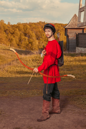 russian hat: Russian archer with the wooden bow in traditional red suit and fur hat. Summer forest on the background. Stock Photo