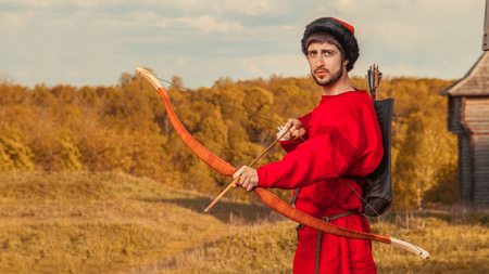 bowstring: Russian archer with the wooden bow in traditional red suit and fur hat. Summer forest on the background. Stock Photo