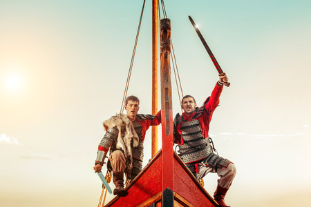 ship bow: Two warriors in armor with the swords on the bow of a sailing ship.