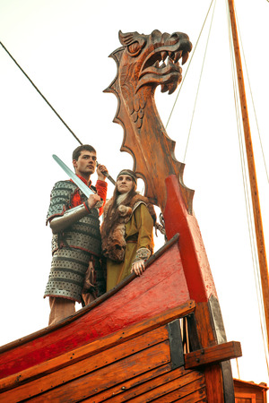 ship bow: Brave north warrior with his beloved are standing on the bow of a ship and looking at the sea.