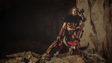 dungeon: Beautiful woman warrior dressed in steel armor is holding an axe and skull. Dungeon on the background.