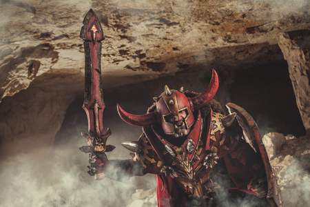 dungeon: Attack of powerful orc knight in heavy armor on the dungeon background.