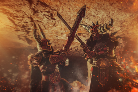 dungeon: Battle of powerful knights in heavy armor on the dungeon background. Flames of the fire on the foreground. Stock Photo
