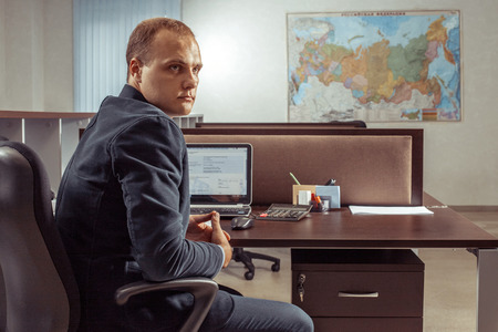 working place: Portrait of the caucasian businessman sitting at the table in office. Stock Photo