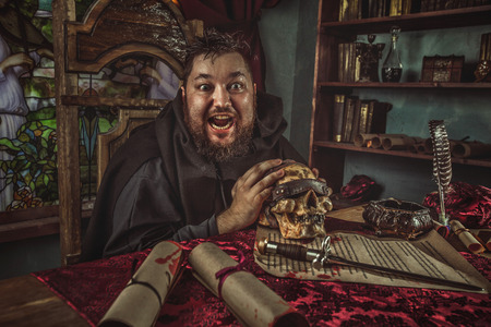 jesuit: Smiling medieval fat monk in sitting in the dark room with the skull. Stock Photo