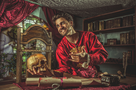 magnate: Smiling medieval grandee is pointing at the skull in the hand. Stock Photo