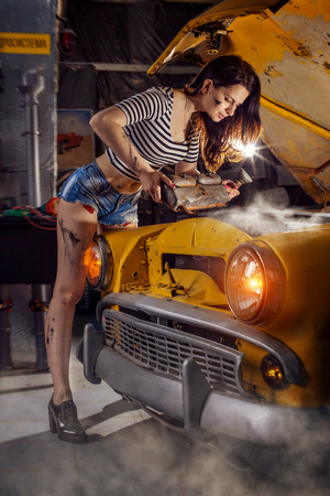 Woman mechanic in shirts is repairing the engine of an old car.