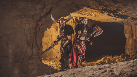 vikings: Couple of vikings in armor with swords. Catacombs on the background. Stock Photo