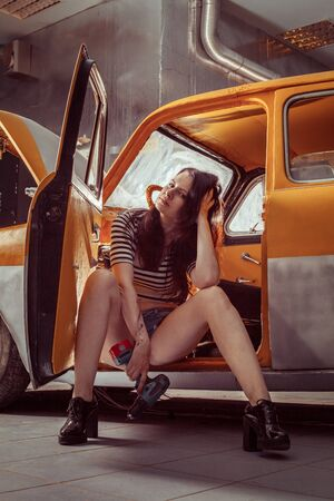 doorstep: Woman mechanic with screwdriver in sexy shirts is sitting on the doorstep of an old car . Stock Photo