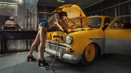 Seksowna kobieta jest coś wewnątrz starego samochodu spawania.