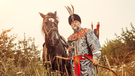 nobleman: Medieval nobleman with the bow in one hand and horse strap in other is hunting in the forest.