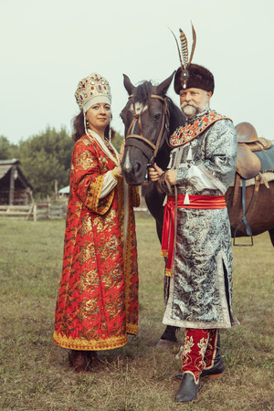 King and Queen dressed in medieval clothes are standing with the horse on the rural summer background.