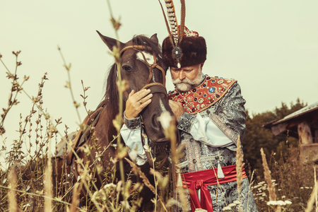 caresses: King dressed in medieval costume is stroking his horse on the rural summer background. Stock Photo