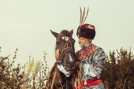 King dressed in medieval costume is stroking his horse on the rural summer background. Stock Photo