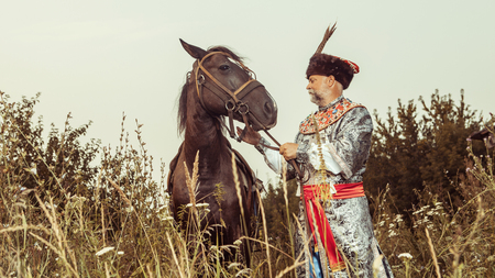 nobleman: King dressed in medieval costume is going to stroke his horse on the rural summer background.