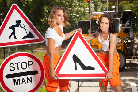 mounting: Two women in orange overalls are mounting  No Men signs on the road.