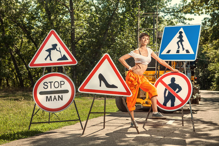 mounting: Woman in orange overalls is mounting  No Men signs on the road.