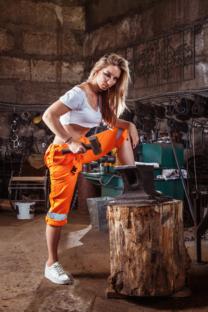 Sexy blond woman in orange pants is working with the hummer and anvil. Workshop on the background.