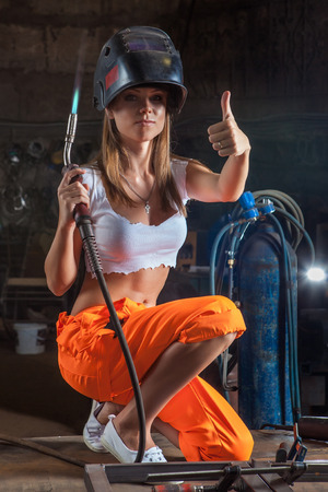 Blond sexy welder woman in the protective mask is looking at the camera and showing thumbs up. Banque d'images