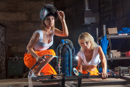 Brigade of two sexy welder women on the workshop background. Imagens